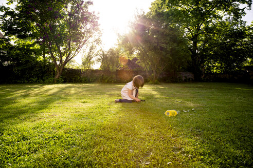 Little girl crouching on a meadow using magnifying glass - LVF003396