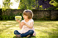 Little girl with insect can sitting on a meadow - LVF003400