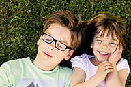 Portrait of boy and his little sister lying on a meadow - LVF003404