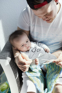 Young father knitting with baby on his lap watching - STKF001214