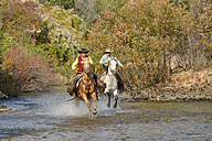 USA, Wyoming, Cowboy and Cowgirl riding their horses across river - RUEF001599