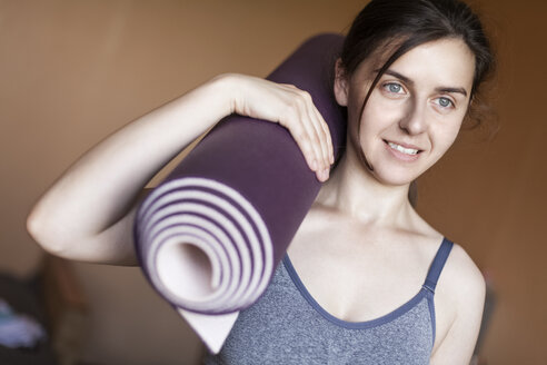 Portrait of smiling woman with yoga mat on her shoulder - BZF000146