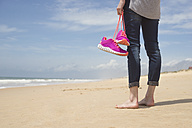 Portugal, Faro, barefoot woman on the beach carrying her pink sneakers - CHPF000143