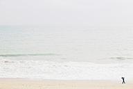 Spain, Mallorca, One person with umbrella walking along the beach - MEMF000745