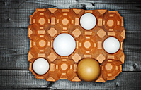 Four brown eggs and a white one in orange egg carton - KSWF001539
