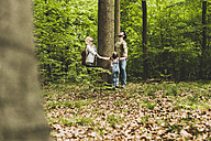 Family in forest standing around tree trunk looking up - UUF004268