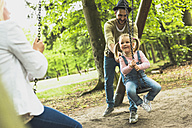 Happy girl with father and mother on playground - UUF004275