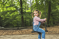Smiling girl sitting on swing - UUF004279