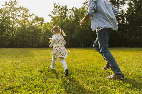 Father and daughter running with paper windmill on meadow - UUF004300