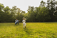 Girl running towards father on meadow - UUF004303