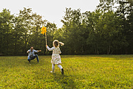 Girl with paper windmill running towards father on meadow - UUF004304