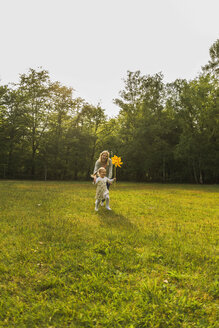 Mother and daughter running with paper windmill on meadow - UUF004307