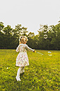 Girl on meadow surrounded by soap bubbles - UUF004318