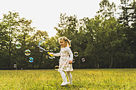Girl on meadow surrounded by soap bubbles - UUF004319