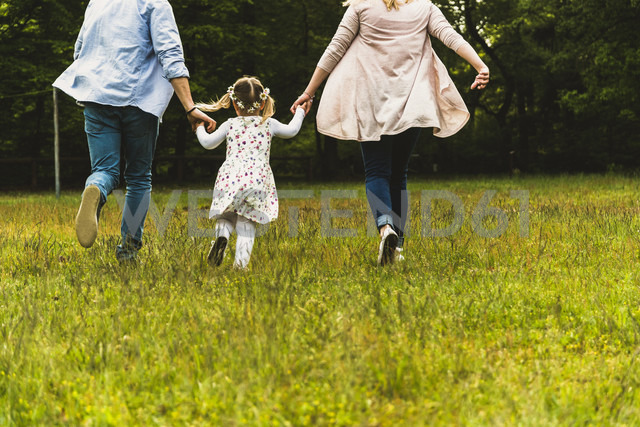 Father, mother and daughter running on meadow - UUF004326