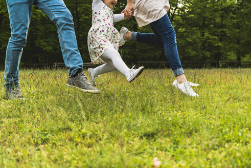 Father, mother and daughter running on meadow - UUF004328