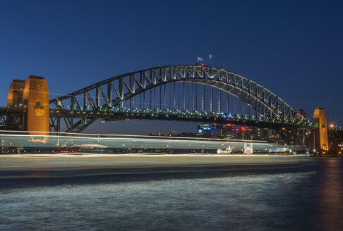 Australia, New South Wales, Sydney, Sydney Harbour Bridge with blurred ferry at dusk - JBF000244