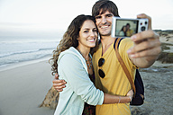 South Africa, happy couple taking a selfie on the beach - TOYF000633