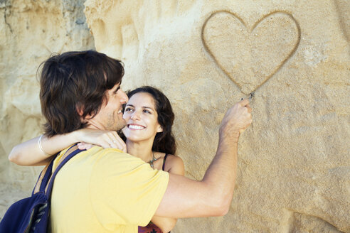 Man with girlfriend drawing heart in rock face - TOYF000650