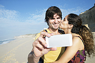 South Africa, happy couple taking a selfie on the beach - TOYF000653