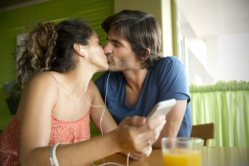 Couple in a cafe kissing and listening to music - TOYF000684