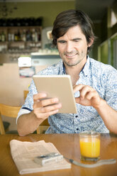 Smiling man in a cafe using digital tablet - TOYF000687