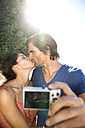 South Africa, kissing couple taking a selfie at the coast - TOYF000694