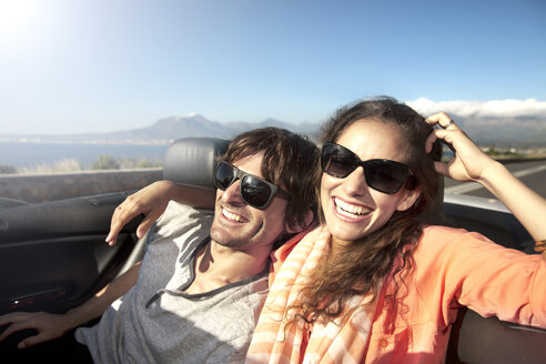 South Africa, happy couple in convertible on coastal road - TOYF000803