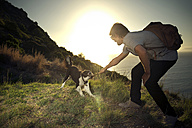 South Africa, man playing with dog at the coast at sunset - TOYF000806