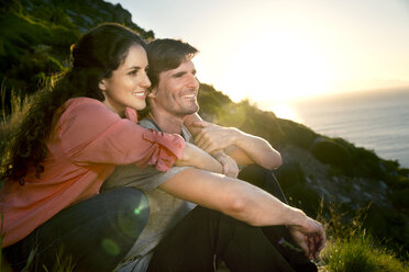 South Africa, couple enjoying the view at the coast at sunset - TOYF000696
