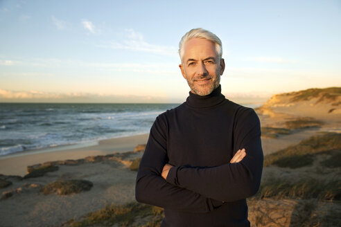 South Africa, portrait of white haired man wearing turtleneck standing on beach dunes before sunrise - TOYF000743