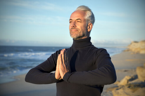 South Africa, portrait of man wearing turtleneck meditating on the beach before sunrise - TOYF000746