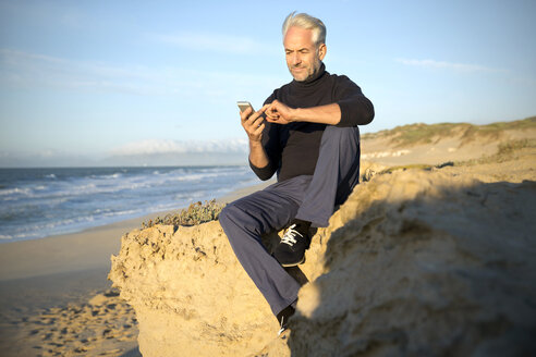 South Africa, portrait of man sitting on a rock at the beach using smartphone - TOYF000749