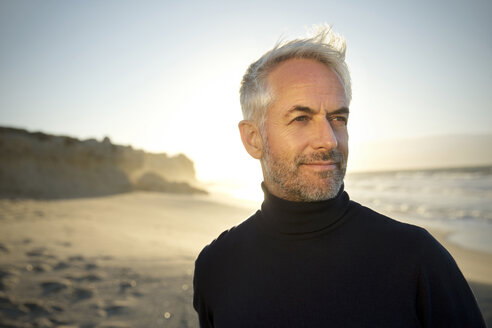 South Africa, portrait of white haired man wearing turtleneck standing on the beach  before sunrise - TOYF000752