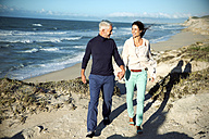 South Africa, couple walking along the coast hand in hand - TOYF000758