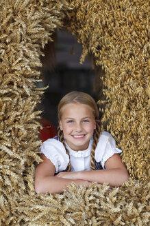 Germany, Luneburger Heide, portrait of smiling blond girl in harvest crown - HRF000026