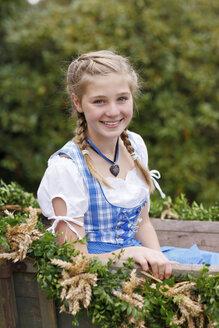 Germany, Luneburger Heide, portrait of smiling blond girl wearing dirndl sitting on harvest wagon - HRF000030