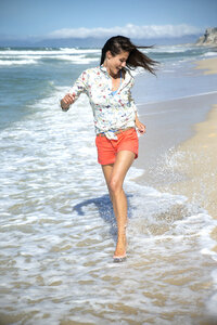 South Africa, happy woman running along the beach at seafront - TOYF000794