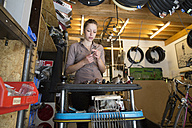 Young woman working in a bicycle repair shop - SGF001605