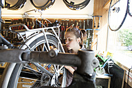 Young woman working in a bicycle repair shop - SGF001607