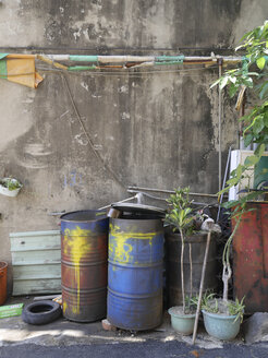 Taiwan, potted plants and old oil drums in a courtyard - JMF000347
