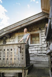 Austria, Salzburg State, Maria Alm, woman standing at alpine hut - NN000352
