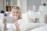 Portrait of smiling blond woman using mini tablet at home - CHPF000146