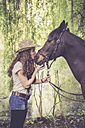 Young woman kissing Arabian horse - SARF001802