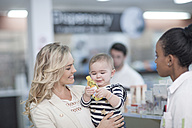 Pharmacist assisting client with baby in drugstore - ZEF005895