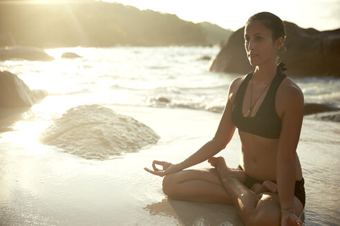 Seychelles, woman meditating at seafront - ABF000609