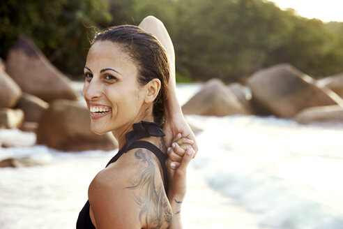 Seychelles, portrait of smiling woman with tatoo doing yoga exercise on the beach - ABF000613