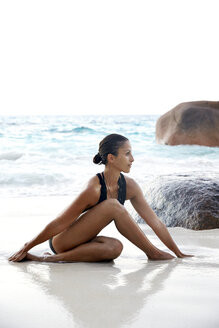 Seychelles, woman doing yoga exercise at seafront - ABF000618