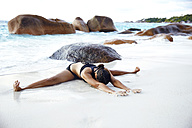 Seychelles, woman doing yoga exercise at seafront - ABF000620