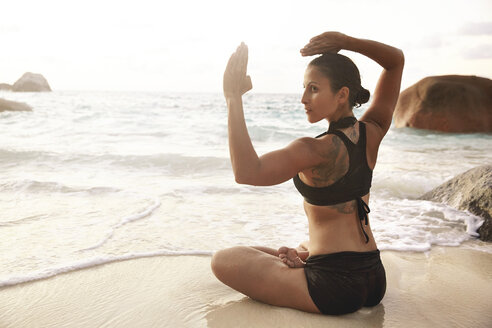 Seychelles, woman doing yoga exercise at seafront - ABF000625